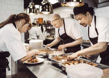 Kvinnlig sous chef och två manliga kockar förbereder maträtter
